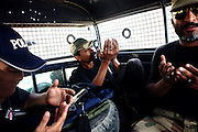Armed members of the AVCC, (Anti-Violence Crime Cell) a special police unit mostly involved in anti-terrorism operations and kidnap cases in the city of Karachi, are reciting prayers in their vehicle on the way to a raid on the outskirts of the city while searching for a kidnap suspect.