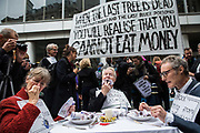 Activists stage a mock dinner and eat fake money outside the offices of Blackrock asset managers during a protest in the City of London, on 14th October 2019. Hundreds of activists blocked roads  in the financial districton Monday, calling out the financial sectors funding of fossil fuels around the world.