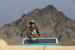 Eid Mohammed 13 cleans the surface of a solar panel on the roof of his home, which is part of the NCA   Solar Power project, Palaj Village, Shahrestan, Daikundi Province, Afghanistan.