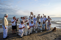 © Licensed to London News Pictures. 24/08/2017. Solent, UK. The trophy is lifted by Royal Southern Yacht Club. Teams take part in the Brambles Bank Cricket Match in the middle of The Solent strait on August 24, 2017. The annual cricket match between the Royal Southern Yacht Club and The Island Sailing Club, takes place on a sandbank which appears for 30 minutes at lowest tide. The game lasts until the tide returns. Photo credit: Ben Cawthra/LNP