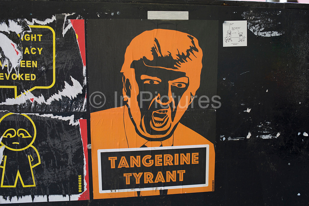 Anti Donald Trump posters in Soho, London, England, United Kingdom. Following the election of President Trump, street art has been springing up regularly in protest, including these orange paste ups.