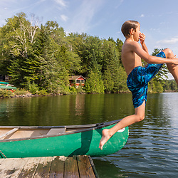 A boy jumps into Island Pond at Red River Camps in Aroostook County, Maine. Deboullie Public Reserve Land.