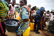Girls carry away a container they just had filled during a UNICEF-sponsored drinking water distribution to flood victims in Cotonou, Benin on Sunday October 24, 2010. The city's water network has been rendered unusable in flooded parts of the city, and many people rely on such water distributions that are carried out by the fire service.