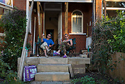 A couple sit with evening drinks on their Edwardian homes front porch during a re-build project, on 1st September 2018, in south London England.