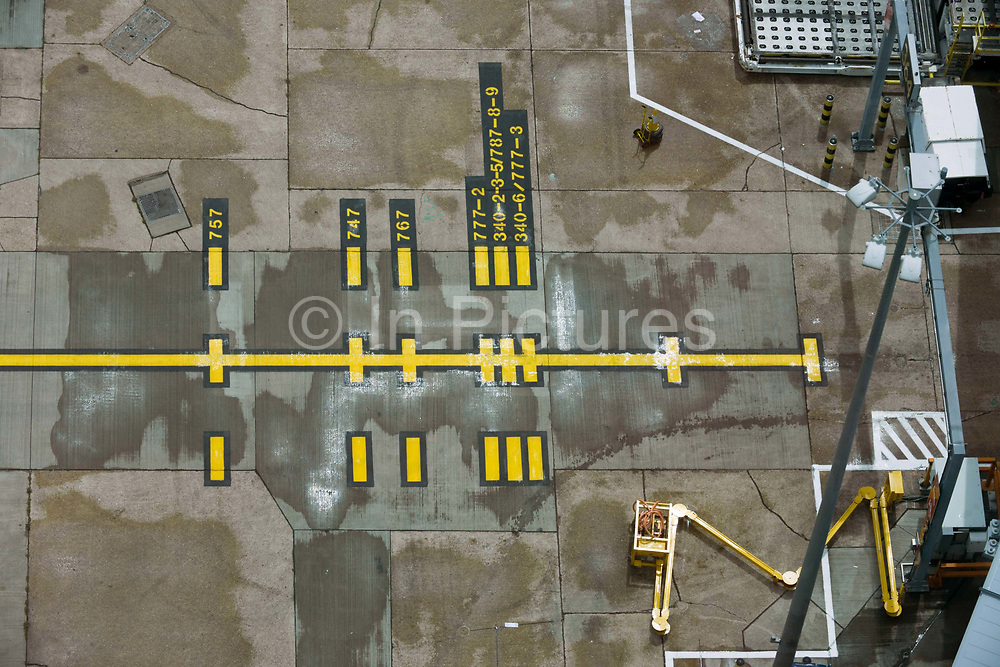 High aerial view (from control tower) of Heathrow airport aviation markings on concrete landscape. Stopping points for the nosewheels of various lengths of wide-bodied airliners are marked on the ground - seen from the top of the control tower. This airport of five terminals on a site that covers 12.14 square kilometres (4.69 sq mi). London Heathrow is a major international airport, the busiest airport in the United Kingdom and the busiest airport in Europe by passenger traffic. It is also the third busiest airport in the world by total passenger traffic, handling more international passengers than any other airport around the globe.