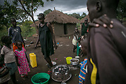 Nyabuol Tut walks amid children while preparing for supper inside Bidibidi refugee settlement in northern Uganda. Nyabuol was gang-raped by Dinka soldiers twice, both in December 2015 and March 2017. She gave birth to Nyalit from the first rape by four soldiers and is eight months pregnant from the second rape by seven armed Dinka men. Her parents were shot to death by Dinka soldiers in between both conflicts in 2013 and 2016.