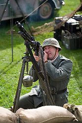 A reenactor dressed as a Panzergrenadier from the 21st Panzer Division living History group uses an MG42 mounted on an anti aircraft tripod at Croft Race Circuits Nostalgia Weekend August 2010. <br /> Images © Paul David Drabble