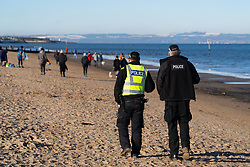 Portobello, Scotland, UK. 24 January 2020. Large numbers of members of the public at Portobello beach and promenade on sunny Sunday afternoon during lockdown. While most people observed social distancing groups of people formed at some of the cafes offering takeaway food and drinks. Police patrols spoke to public sitting down and in groups at cafes to ask them to move on. Iain Masterton/Alamy Live News