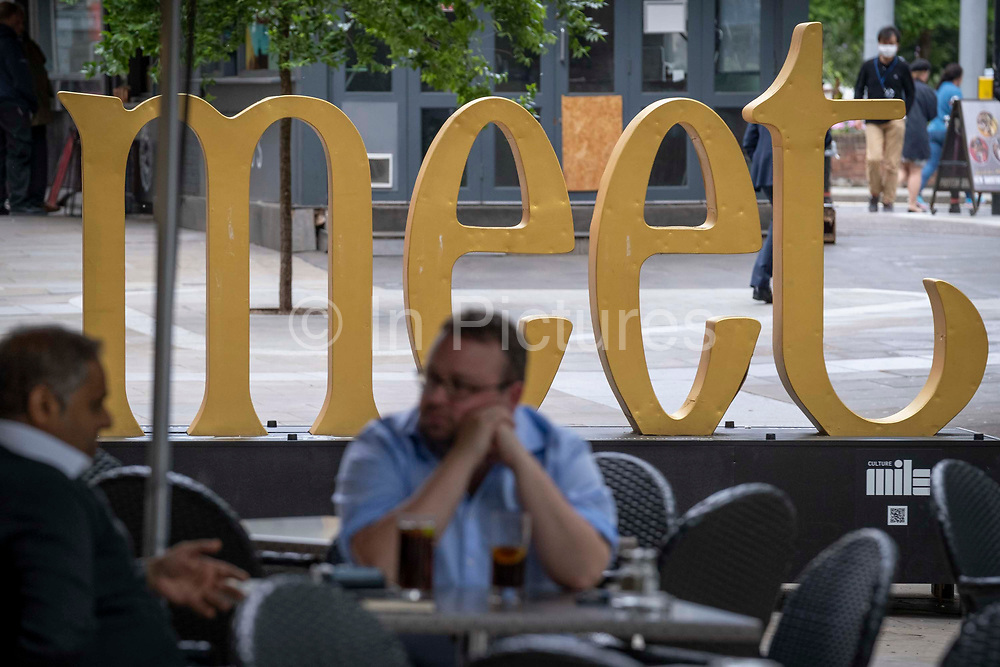 With the word Meet in the background, two businessmen chat at a table outside a City bar, in the City of London, the capitals financial district, on 22nd June 2021, in London, England.