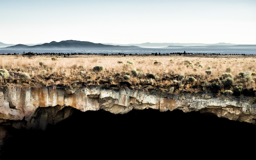 The world is flat and this is the edge!<br /> Much of central Oregon is covered in ancient lava beds and lava tubes are plentiful in some areas. A lava tube is formed when hot lava flows out of a surrounding mass that has cooled. When the flow stops a tube remains – otherwise known as a lava cave. In this instance the roof of a lava tube has collapsed, leaving a hole in the ground about 60 feet across. I positioned myself on one side of the hole and shot across the abyss.