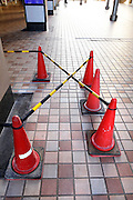 safety cones with bars blocking part of a pedestrian walkway