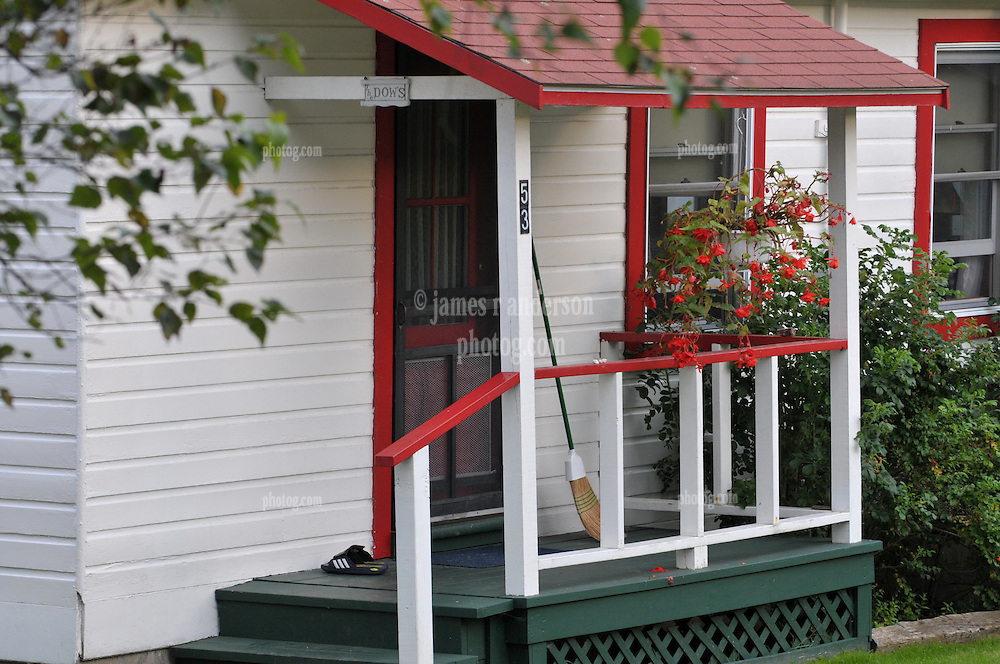 Potts Point South Harpswell, Maine. Front Porch and Broom. Red Trim, Green Deck and White Clapboard. Credit Photography: James R Anderson