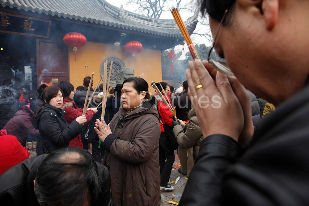 Worshippers crowd into Longhua temple to make their Chinese New Year prayers and well-wishes in Shanghai, China on 26 January, 2009.  Traditionally the first day of the lunar new year is an auspicious day to offer prayers and honor ancestors.