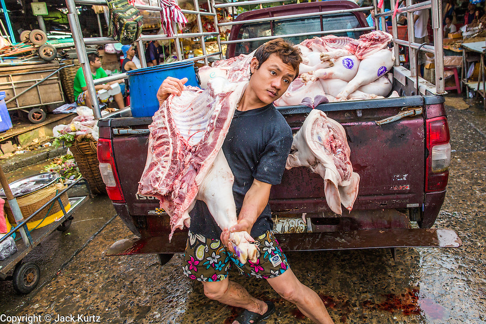 """26 SEPTEMBER 2012 - BANGKOK, THAILAND:  A man lifts a side of pork out of a truck to deliver it to a butcher shop in Khlong Toey Market in Bangkok. Khlong Toey (also called Khlong Toei) Market is one of the largest """"wet markets"""" in Thailand. The market is located in the midst of one of Bangkok's largest slum areas and close to the city's original deep water port. Thousands of people live in the neighboring slum area. Thousands more shop in the sprawling market for fresh fruits and vegetables as well meat, fish and poultry.    PHOTO BY JACK KURTZ"""