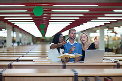 Three students with laptop in library (Credit Image: © Image Source/Albert Van Rosendaa/Image Source/ZUMAPRESS.com)