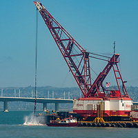 A massive floating drege maintains critical shipping channels in California's San Francisco Bay.  The Bay Bridge rises behind it