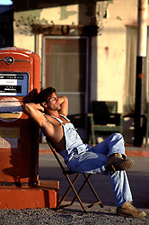 hot man in overalls and no shirt leaning against a retro gas station pump