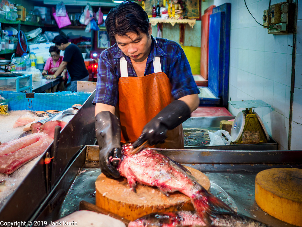 """26 FEBRUARY 2019 - BANGKOK, THAILAND: A fish monger cleans a fish for a customer in Bangkok's Chinatown. Bangkok has one of the largest """"Chinatown"""" districts in the world. About 14% of all Thais have some Chinese ancestry and Chinese cultural practices are incorporated in many facets of Thai daily life.       PHOTO BY JACK KURTZ"""