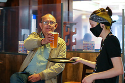 © Licensed to London News Pictures. 17/05/2021. London, UK. A barmaid serves a pint of beer to a pub goer in The Toll Gate - JD Wetherspoon pub, north London, as step three of the government's roadmap to ease the Covid-19 restrictions goes live, allowing for indoor hospitality to reopen, with table service only as people are not able to order from the bar. Photo credit: Dinendra Haria/LNP