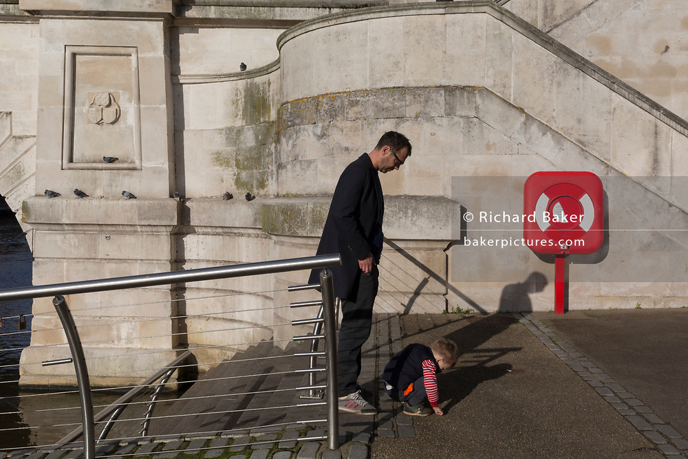 Next to a life buoy, a father waits for his child to finish exploring the pavement on the riverside beneath Kingston Bridge, on 7th November 2019, in Kingston, London, England