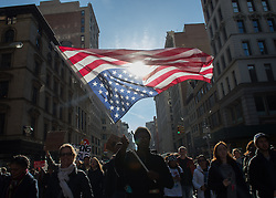 November 12, 2016 - New York, New York, U.S. - A demonstrator carries the American flag upside down as  thousands of people rally and march to Trump Tower in protest of president-elect Trump. (Credit Image: © Bryan Smith via ZUMA Wire)