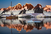 Expedition yacht Pelagic Australis moored in bay near Pleneau and Hoovgard Islands - sunset reflection of peaks on Booth Island behind - Antarctic Peninsula March 2020