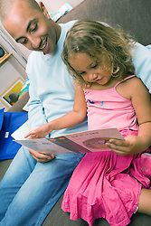 Father reading a book with his young daughter,