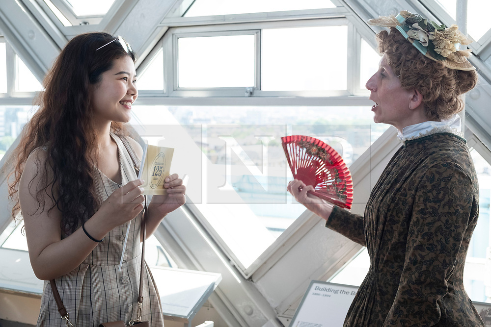 © Licensed to London News Pictures. 30/06/2019. London, UK. A visitor talks with an actor dressed in Victorian period costume, re-enacts scenes which might have happened during the construction of Tower Bridge. The London landmark celebrates its 125th anniversary today and was open on 30 June 1894. Photo credit: Ray Tang/LNP