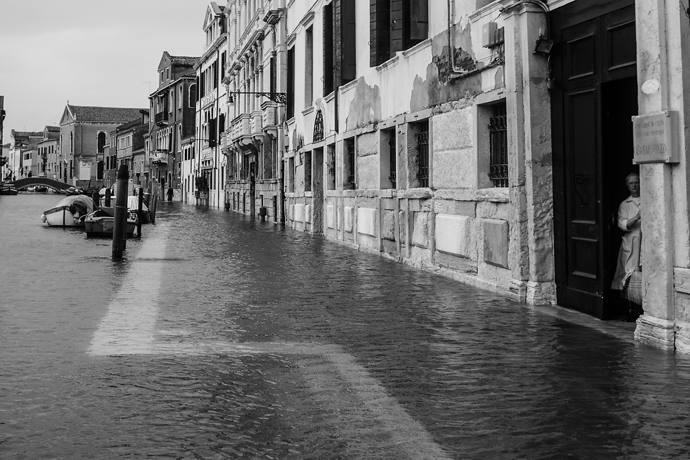 Venice, Italy. 29 October, 2018. A nun sweeps out the water from the entrance of the convent during the high tide in Cannaregio district on October 29, 2018, in Venice, Italy. This is a selection of pictures of different areas of Venice that the press has not covered, were resident live and every year they have to struggle with the high tide. Due to the exceptional level of the 'acqua alta' or 'High Tide' that reached 156 cm today, Venetian schools and hospitals were closed by the authorities, and citizens were advised against leaving their homes. This level of High Tide has been reached in 1979. © Simone Padovani / Awakening / Alamy Live News