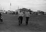 Harry Bradshaw (left), Portmarnock and N.C. Lynch, Sutton, make their way to the 1st tee from the clubhouse at the Irish Dunlop £1,000 Tournament at Tramore Golf Club, Co. Waterford on the 19th August 1967.
