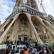 """Barcelona, Spain - February 20, 2018 - Tourists viewing the Passion Facade at the Temple Explatori de la Sagrada Familia in Barcelona, Spain. The ground breaking took place in 1882 and the structural work and decorations continue to this day. The designer of this amazing UNESCO World Heritage Site is Catalan architect Antoni Gaudi (1852-1926). On the subject of the extremely long construction period, Gaudi once remarked: """"My client is not in a hurry.""""<br /> <br /> Image: © Rod Mountain http://www.rodmountain.com<br /> Nikon D800 / Nikkor Lens<br /> <br /> @spain @barcelona_cat @visitbarcelona @basilicasagradafamilia <br /> <br /> @spain.info @bcn.cat @BasilicadelaSagradaFamilia @visitbarcelona<br /> <br /> @spain @barcelona_cat @sagradafamilia @VisitBCN_EN<br /> <br /> https://en.wikipedia.org/wiki/Sagrada_Fam%C3%ADlia<br /> https://sagradafamilia.org<br /> https://www.barcelona.cat/en/<br /> https://www.barcelonaturisme.com/wv3/en/<br /> https://en.wikipedia.org/wiki/Barcelona<br /> https://www.spain.info/en/que-quieres/ciudades-pueblos/grandes-ciudades/barcelona.html<br /> https://www.spain.info/en/<br /> <br /> #beautiful #lookingup #perspective #creative_architecture #guadi #FriendsinBNW  #blackandwhitephoto #bnw_captures #bnw_society #blacknwhitepic #bnw_barcelona #TravelAwesome #Travelingpost #momentsofmine #tourists #pilgrimage #theglobewanderer#roamtheplanet #Faith #passion #Christ #goodfriday #eastersunday #church #culture #Spain #TourismSpain #VisitSpain #Barcelona #sagradafamilia"""