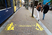keep your 1.5 meter distance sign on the pavement in Amsterdam by a tram stop in the Leidsestraat
