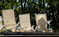 """SPA, BELGIUM - AUGUST-13-2005 -  A client relaxes outside in a lounge chair while reading a newspaper, under the lush green trees that surround Les Thermes de Spa. Health and beauty spas the world over, take their name from the original spa in Spa, Belgium where visitors have been coming for hundreds of years to """" take the waters """" at Les Thermes de Spa . (Photo © Jock Fistick)"""