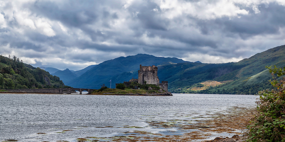 Eilean Donan offers one of the most iconic images of Scotland. It is situated on an island at the point where three great sea lochs meet, and surrounded by some majestic scenery.<br /> <br /> First inhabited around the 6th century, the first fortified castle was built in the mid 13th century and stood guard over the lands of Kintail. Since then, at least four different versions of the castle have been built and re-built as the feudal history of Scotland unfolded through the centuries.<br /> <br /> Partially destroyed in a Jacobite uprising in 1719, Eilean Donan lay in ruins for the best part of 200 years until Lieutenant Colonel John MacRae-Gilstrap bought the island in 1911 and proceeded to restore the castle to its former glory. After 20 years of toil and labour the castle was re-opened in 1932.<br /> <br /> This photograph is a panoramic colour version of the view of Eilean Donan Castle from the north, on Loch Alsh through to Loch Duich. The photograph can be purchased as print, mounted print in frames, canvas or aluminum or as a digital file.