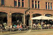 People sitting in sunshine outside cafe Bryggen area, Bergen, Norway