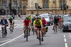 © London News Pictures. 25/08/2016. The majority of cyclists ignore the cycle lane (pictured left) on Parliament Square in Westminster, London. Cyclists repeatedly ignore new cycle lanes installed around westminster in central London. Between the hours of 8am and 9am on Wednesday 24/08/2016, 266 (two hundred and sixty six) cyclists passed through the red light at one of the newly installed bike lanes and only 15 (fifteen) cyclists stopped.  The light system is designed to allow either vehicles or cyclists to pass at one time in order to make the junction safer for cyclists..... **VIDEO AVAILABLE** Photo credit: London News Pictures.