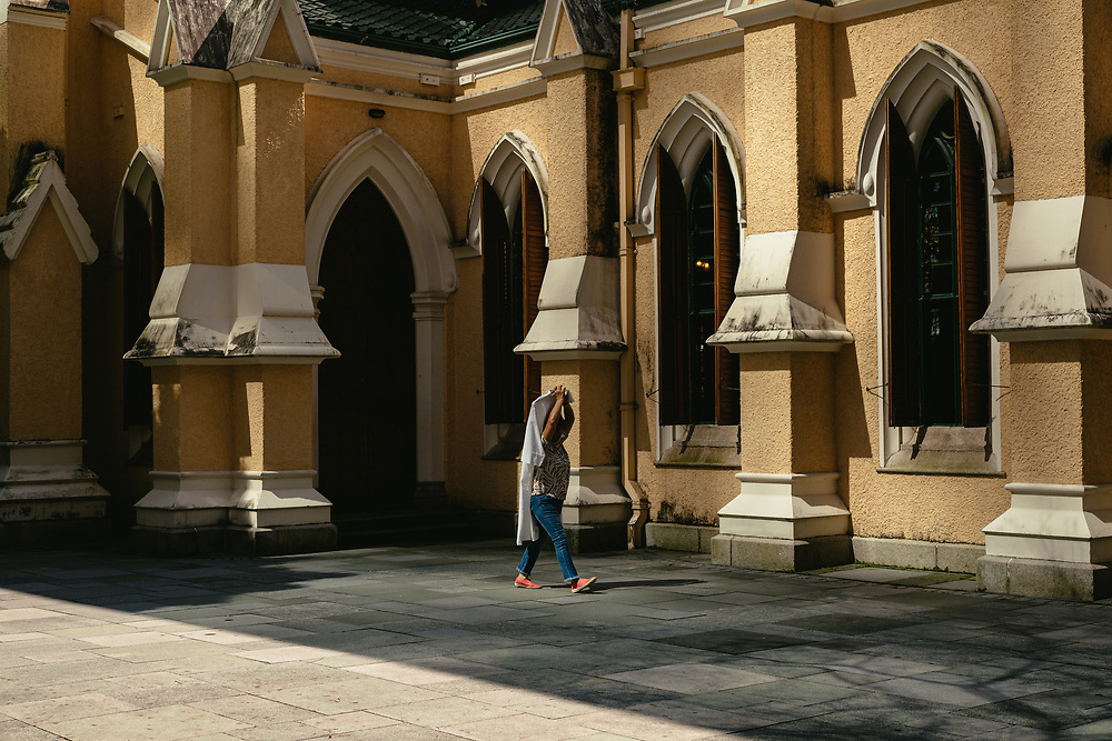 A woman carries a clothing item as she walks past St. John's Cathedral, in Central, Hong Kong Island, on October 15, 2019.
