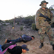 Armed citizen patrol along the U.S.-Mexico border in San Diego, California in an effort to stop undocumented migrants from entering the U.S. from Mexico. Here, a vigilante detains a couple migrants after they were stopped. Please contact Todd Bigelow directly with your licensing requests. PLEASE CONTACT TODD BIGELOW DIRECTLY WITH YOUR LICENSING REQUEST. THANK YOU!