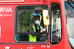 © Licensed to London News Pictures. 17/04/2020. London, UK. A bus driver wearing a face mask and plastic gloves as a precaution against the COVID-19 as coronavirus lockdown continues. The Mayor of London, Sadiq Khan has called for all passengers to wear face masks on public transport after 26 TfL workers, including 16 bus drivers, have died from COVID-19. Photo credit: Dinendra Haria/LNP