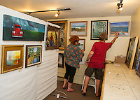 Marie Kelly and Rob Caron hang artwork during Wednesday evening's setup for the Lakes Region Art Assocation's Art Show at VynnArt in Meredith.  (Karen Bobotas/for the Laconia Daily Sun)
