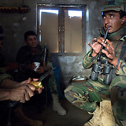 A Afghan soldier plays a flute while others peel potatoes on the front lines in the Howz-E-Madad area a day before a joint operation against Taliban insurgents with Canadian Forces in Zharay District, Kandahar Afghanistan which along with nearby Panjwa'i are the most volatile areas in the country and the scene of heavy fighting with Taliban insurgents up through 2010, which has become the site of some of the largest land battles in NATO's history.<br /> © Louie Palu/ZUMA Press/New America Foundation