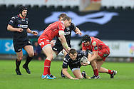 Dan Biggar of the Ospreys (c)  , on as a replacement, tries to set up an attack but is stopped by James Davies of the Scarlets (r). Guinness Pro12 rugby match, Ospreys v Scarlets at the Liberty Stadium in Swansea, South Wales on Saturday 26th March 2016.<br /> pic by  Andrew Orchard, Andrew Orchard sports photography.