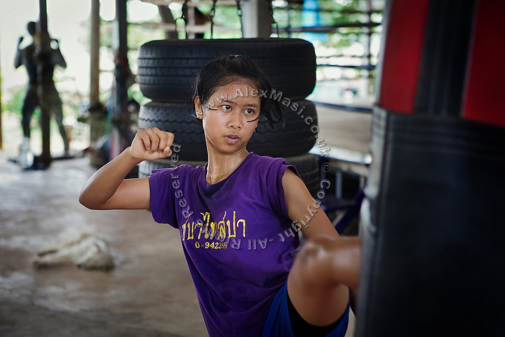 Phatsorn Bunmasen, 14, is practicing high kicks in the gym where she trains in Muay Thai boxing, in a village near Ubon Ratchathani, northeast Thailand.