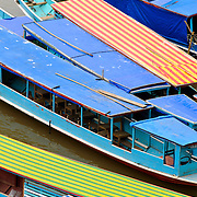 Colorful boats are moored on the banks of the Nam Ou (River Ou) in Nong Khiaw in northern Laos. Shot from above, the boats are brightly colored and have different textures.
