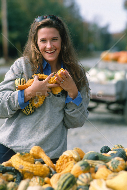 woman at a vegetable stand holding squash