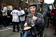 A disabled competitor at the Great Spitalfields Pancake Race on Shrove Tuesday, pancake day, at the Old Truman Brewery, London, UK. This is a fun quirky annual event where competitors come as teams of four people dressed up in costume of some kind. Organised by Alternative Arts raising money for charity.