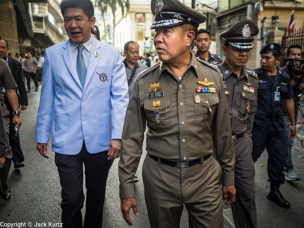 18 AUGUST 2015 - BANGKOK, THAILAND: Thai police chief SOMYOT PUMPUNMUANG walks around the neighborhood near Erawan Shrine Tuesday during the investigation of the bombing of the shrine.  An explosion at Erawan Shrine, a popular tourist attraction and important religious shrine in the heart of the Bangkok shopping district killed at least 20 people and injured more than 120 others, including foreign tourists, during the Monday evening rush hour. Twelve of the dead were killed at the scene. Thai police said an Improvised Explosive Device (IED) was detonated at 18.55. Police said the bomb was made of more than six pounds of explosives stuffed in a pipe and wrapped with white cloth. Its destructive radius was estimated at 100 meters.    PHOTO BY JACK KURTZ