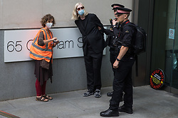 City of London Police arrest an environmental activist from Extinction Rebellion who spread fake blood outside the offices of law firm Debevoise & Plimpton LLP during a Blood Money March through the City of London on 27th August 2021 in London, United Kingdom. Extinction Rebellion were intending to highlight financial institutions funding fossil fuel projects, especially in the Global South, as well as law firms and institutions which facilitate them, whilst calling on the UK government to cease all new fossil fuel investment with immediate effect.