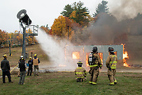 Members of the Gunstock snowmaking crew and Gilford Fire watch as the remainder of the Phelps Barn burns on Saturday afternoon following a series of fire fighting training sessions.  (Karen Bobotas Photo/for The Laconia Daily Sun)