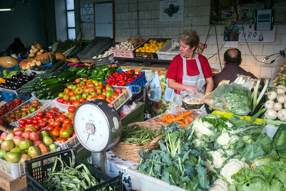 A woman setting up her vegetable stall in the Mercado do Bolhão, Porto, Portugal. One of the most emblematic buildings of the city with wrought iron architecture over two floors, the market dates back to 1839.